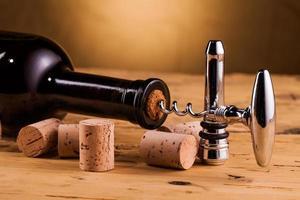 garrafa de vinho e saca-rolhas na mesa foto