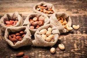 misture nozes na mesa de madeira, comida vegana saudável. foto
