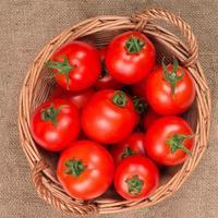 tomates na cesta na vista superior do saco de estopa foto