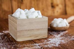 cubos de açúcar em uma tigela com o açúcar derramado foto