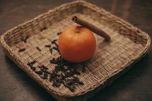 tangerinas e pau de canela em fundo de madeira vintage foto