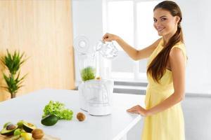 Alimentação saudável. mulher vegetariana preparando suco de desintoxicação verde. dieta foto