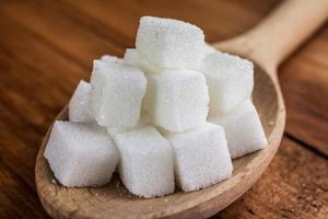 cubos de açúcar na colher de pau sobre fundo de madeira foto