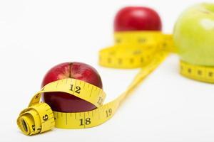 maçã vermelha e fita métrica foto