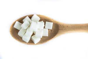 cubos de açúcar na colher no fundo branco isolado foto