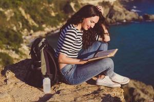 Mulher bonita sentada no pico da rocha lendo um livro foto