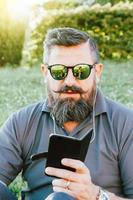 homem hippie adulto estiloso usando um smartphone ao ar livre foto