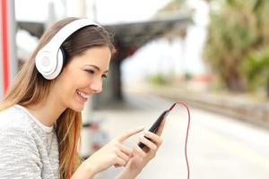 menina adolescente ouvindo música com fones de ouvido esperando o trem foto