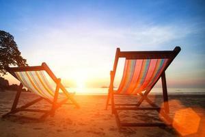 espreguiçadeiras na praia deserta à beira-mar foto