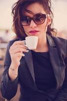 jovem e linda mulher bebendo café em um café foto