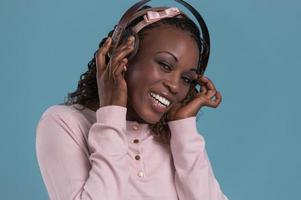 mulher africana feliz ouvindo música em fones de ouvido.