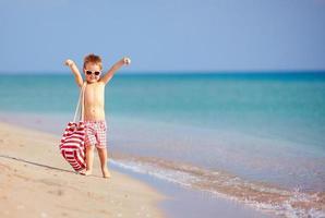 criança feliz caminhando na praia de verão