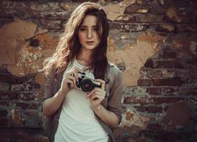mulher em pé perto da parede segurando uma câmera retro,