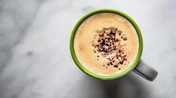 xícara de café verde e branco sobre fundo de mármore foto