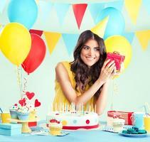 linda mulher segurando um presente na festa de aniversário foto