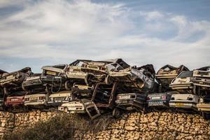 pilha de restos de carros enferrujados danificados no ferro-velho