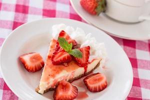 pedaço de cheesecake com morangos frescos fatiados foto