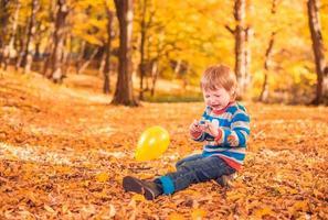 menino chorando na floresta de outono
