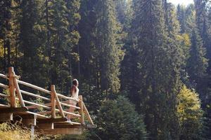 garota no deck de observação em uma floresta de pinheiros