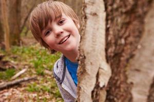 retrato de menino jogando na floresta foto