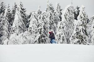 casal homem mulher caminhada na neve na floresta de inverno foto