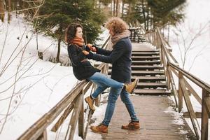 casal hipster se divertindo na floresta de inverno foto