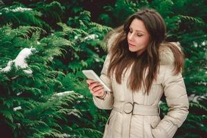 garota na floresta olhando para o telefone sério foto