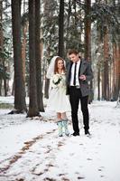 noiva e noivo caminhando na floresta de inverno foto