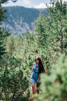 mulher de cabelo comprido viajando na floresta de abetos foto