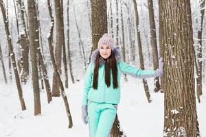 linda jovem caminhando na floresta de inverno