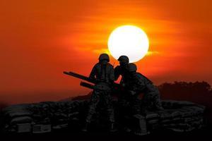 metralhadora anti-aérea e três soldados em silhueta foto