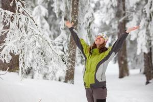Mulher bonita posando em floresta congelada de inverno