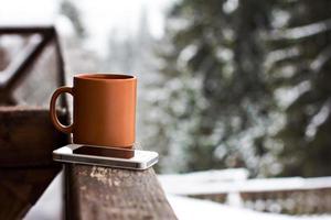 copo com bebida quente sobre fundo de floresta de inverno foto