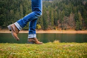 mulher de botas e jeans caminha ao longo da margem do lago