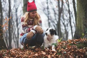 jovem e seu cachorro posando ao ar livre na floresta foto