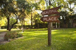 """placa de jardim de madeira onde se lê """"lindo lugar"""", apontando para baixo"""