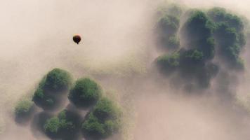 aérea de balão de ar quente flutuando acima da floresta enevoada.