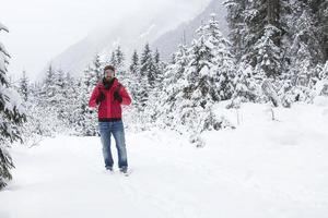 jovem com óculos de neve, caminhando em uma floresta de inverno foto