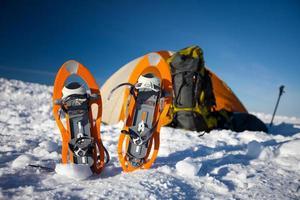 sapatos de neve deixados na frente de uma tenda laranja na floresta de inverno foto