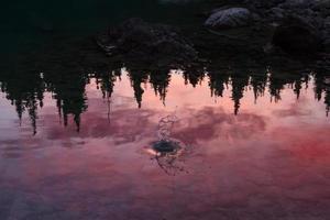 pôr do sol refletido em um lago de montanha foto