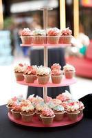 torre de cupcakes com cobertura de enfeite no fundo desfocado foto