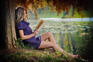 linda jovem lendo em uma floresta outonal foto