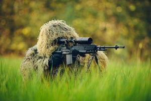 atirador em traje de camuflagem olhando para o alvo