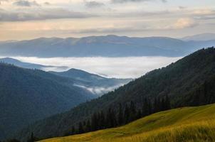 montanhas com nevoeiro ao nascer do sol foto
