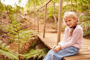 jovem sorridente sentada na ponte de madeira em uma floresta foto