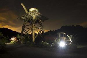 luz fantasmagórica vindo de um carro abandonado na cidade fantasma foto