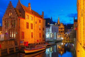 paisagem urbana com o pitoresco canal noturno dijver em bruges foto