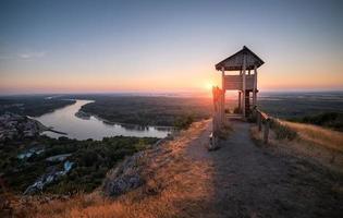 torre de observação turística de madeira acima de uma pequena cidade com rio