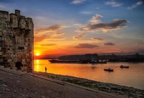 pescador no pôr do sol em dois barcos e no fundo da torre antiga foto