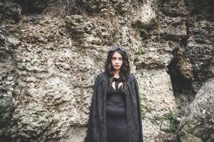 Mulher linda vampira escura com manto preto e capuz